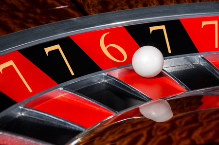 wheel spin: Concept of classic casino code 7-7-6-7-7 lucky numbers roulette wheel with black and red sectors and white ball Stock Photo