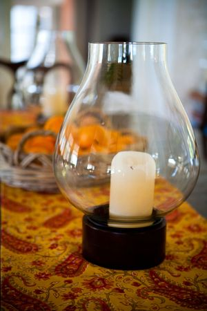 Candle in a lantern on a paisley table clothe Stock Photo