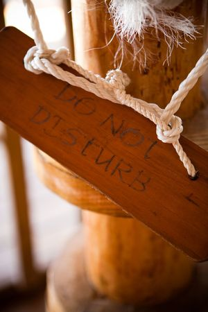 Do not disturb sign made of wood haging from post
