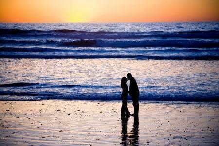 parejas caminando: Pareja bes�ndose en la playa