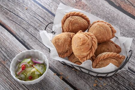 Traditional curry puffs stuffed chicken on wooden table as background.