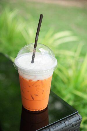 Thai milk tea topping cream cheese in glass plastic Imagens