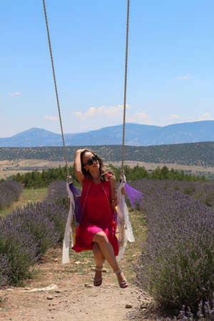 Turkish woman in brunette pink dress with brunette sunglasses sitting on swing in lavender field under sky, copy space