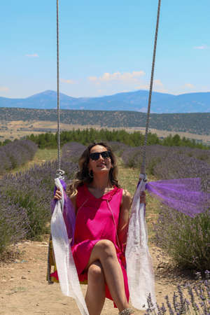 Turkish woman in brunette pink dress with brunette sunglasses sitting on swing in lavender field under sky, copy space Imagens