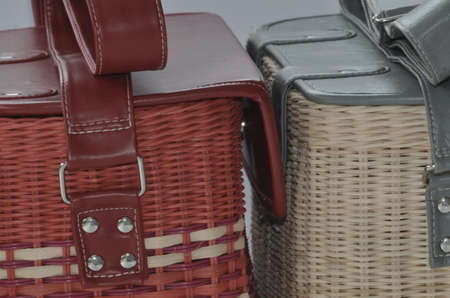 A close-up of modern handmade box-shaped bags made from rattan with leather cover and straps. Selective focus