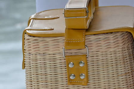 Close-up of a modern handmade box-shaped bags made from rattan with leather cover and straps. Selective focus