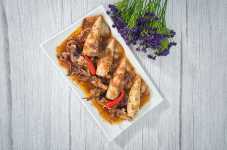 A serving of squid sambal on a white plate. Selective focus points. Blurred background