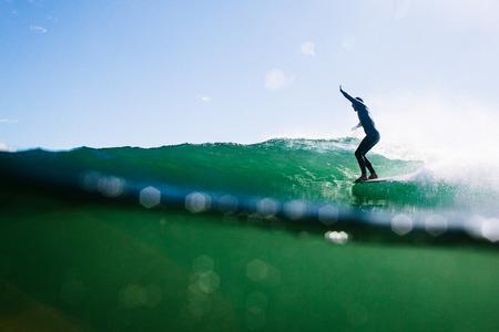 Overunder shot of longboard surfer hanging ten Stock Photo