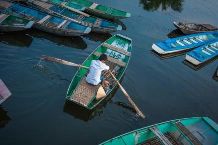 Young man rowing boat  Van Lam Wharf, Tam Coc Grotto, Ninh Binh Province, Vietnam