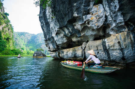 The woman is paddling groceries and fresh flowers boat  Tam Coc Grotto, Ninh Binh Province, Vietnam Editorial