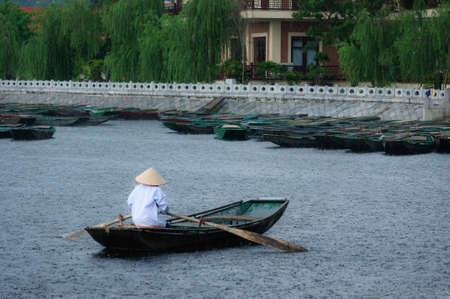 The girl rowing in rain  Van Lam Wharf, Tam Coc Grotto, Ninh Binh Province, Vietnam Stock Photo