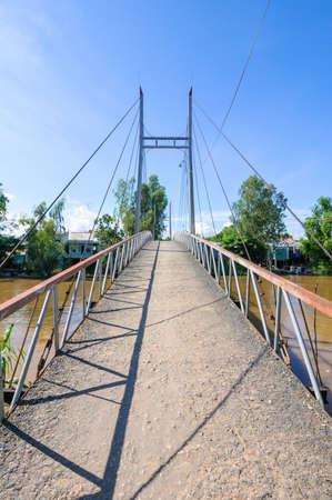 Small suspension bridge leading to a small village, Mekong Delta, Vietnam