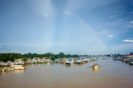Aquaculture on floating houses on the river, a rainbow in the sky  Mekong Delta, An Giang Province, Vietnam Stock Photo