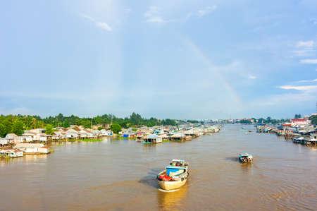 Floating village and transport boat on river, Mekong Delta, Vietnam