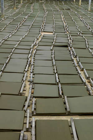 Not yet calcined clay bricks in lines, brick factory  Stock Photo