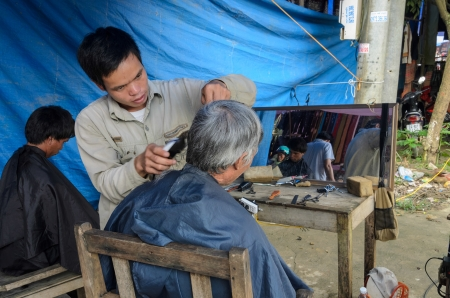 BAC HA TOWN, LAO CAI, VIETNAM - SEPTEMBER 11  Unidentified barber cutting hair for customer at sunday market on September 11, 2011 in Bac Ha Town, Vietnam  This is a most famous sunday market in north of Vietnam