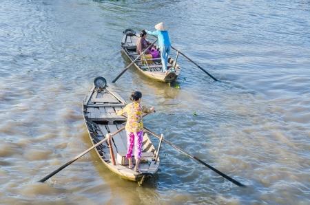 Ferry-woman paddling at Nga Nam Floating Market, Vietnam