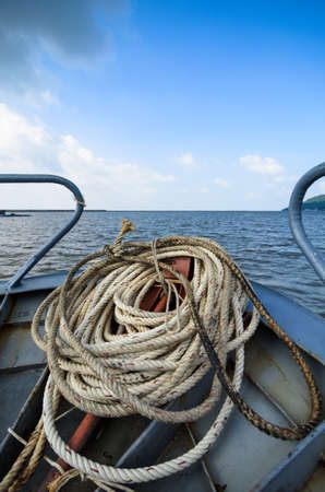 Close-up windings of rope at the head of the boat, on the sea, blue sky with clouds, Vietnam photo