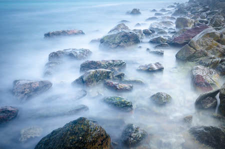 Slow exposure waves and rocks on the beach photo
