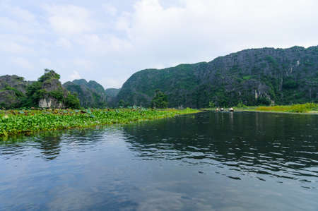 Tourists, limestone cliffs, Ngo Dong river in Tam Coc Grotto, Ninh Binh Province, Vietnam photo