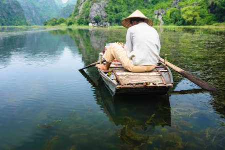 Shadow of woman on groceries boat reflection in water in Tam Coc Grotto, Ninh Binh Province, Vietnam Stock Photo