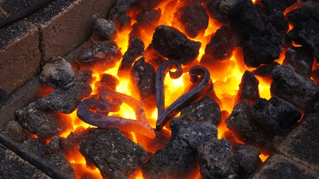 ancient blacksmith: Two metal hearts in hot fire                        Stock Photo