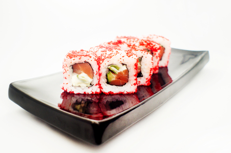 menu land: sushi roll with red tobiko platted on a black plate