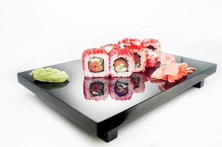 sushi roll with red tobiko platted on a black plate
