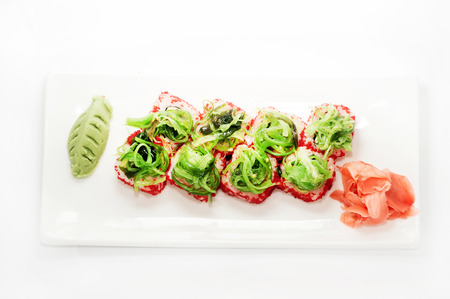 the land of menu: Red tobiko sushi roll platted on a white plate.