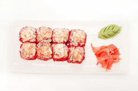menu land: Red tobiko sushi roll platted on a white plate.