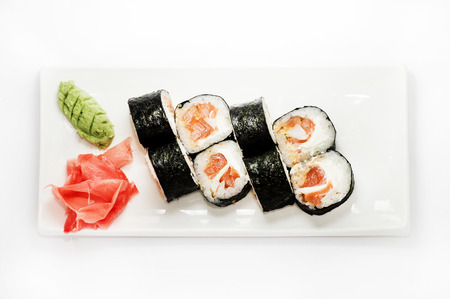 menu land: Sushi with salmon wrapped in nori on a white plate