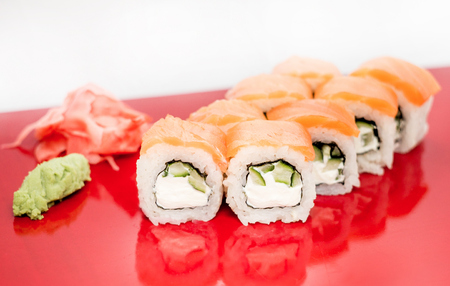the land of menu: Philadelphia sushi roll platted on a red plate