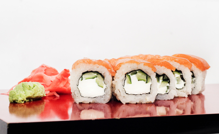 Philadelphia sushi roll platted on a red plate