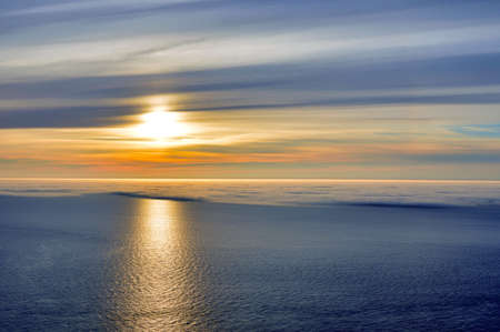 Great sunset of the Midnight Sun, from Nordkapp, Norway, with half of the water covered with sea fog.