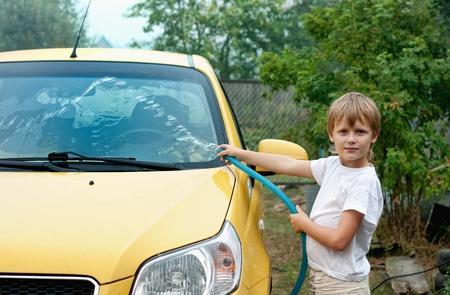 Little boy washing yellow car.