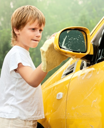 Little boy washing yellow car.