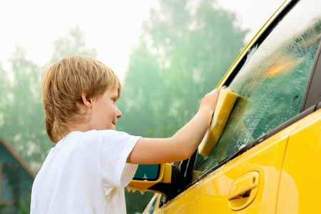 chores: Little boy washing yellow car.