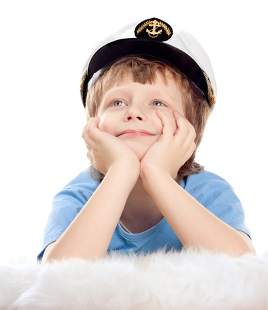 Cute dreaming child in captain cap lies on soft sheep fur isolated over white background. High key. Stock Photo