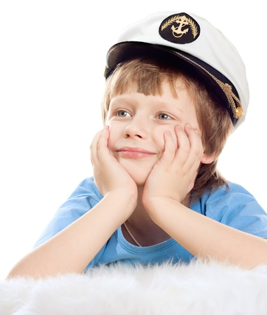 Cute dreaming child in captain cap lies on soft sheep fur isolated over white background. High key. photo