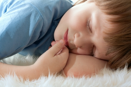 dark blond: Cute boy sleeping on white fur. Sleep well.
