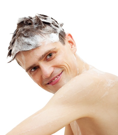 Man with shampoo over hair in shower isolated on white background.