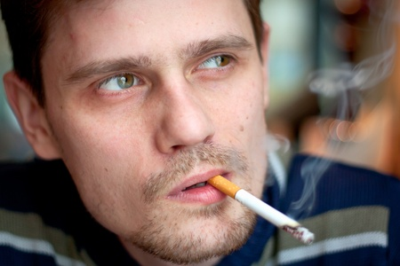 The middle-age man smokes a cigarette in the bar. Focus on the eyes.