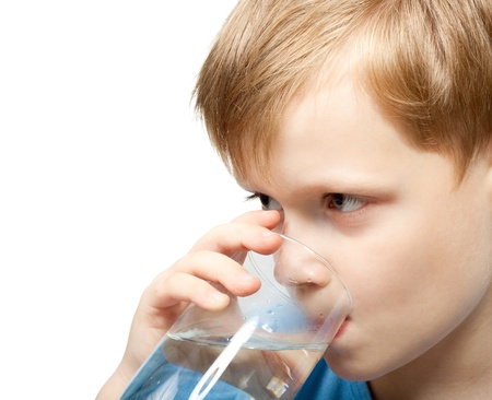 Little boy drink cold water from the glass. Closeup.