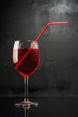In a bar of vampires. Cocktail on the basis of blood. A glass with a red liquid and red pipe on black grunge background.