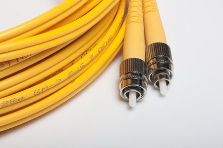Telecommunication background.Twisted fiber optic single mode FC jack over gray background. Stock Photo - 9467860