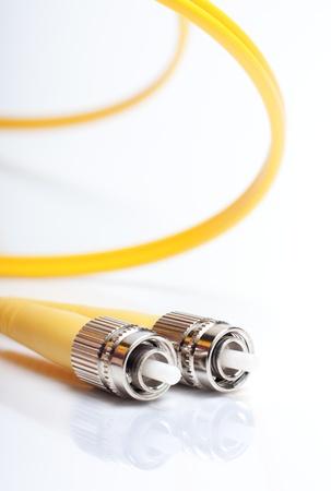 Telecommunication background.Twisted fiber optic single mode FC jack over gray background. Stock Photo