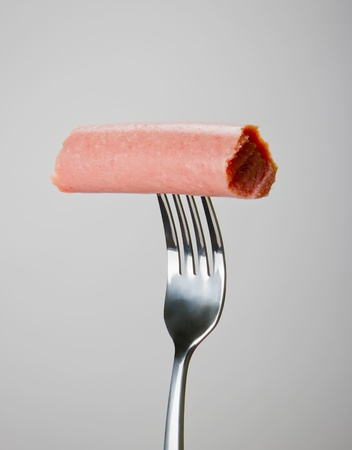 Sausage on the fork over gray background. photo