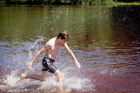 Man having fun running through the water in the river water in summer.