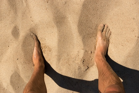 Legs of man standing in the sand on a wild beach. The view from the top.