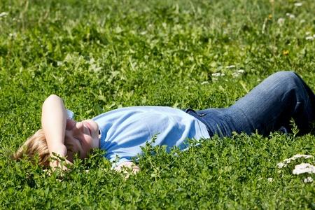 lying on grass: Boy have fun in green grass.